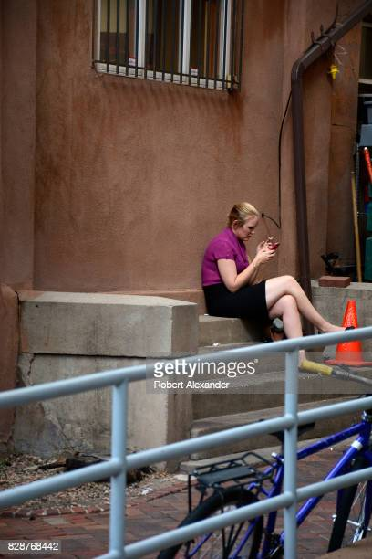 A young woman takes a break from her job to use her smartphone and smoke a cigarette in Santa Fe New Mexico