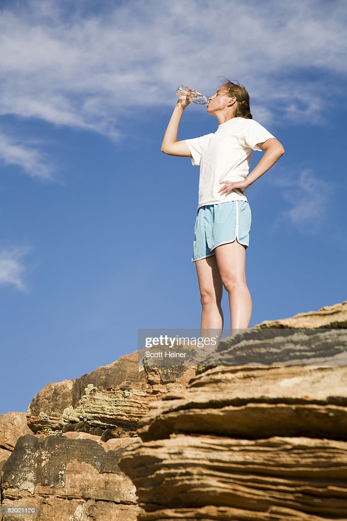 Young woman takes a drink of water after a run.