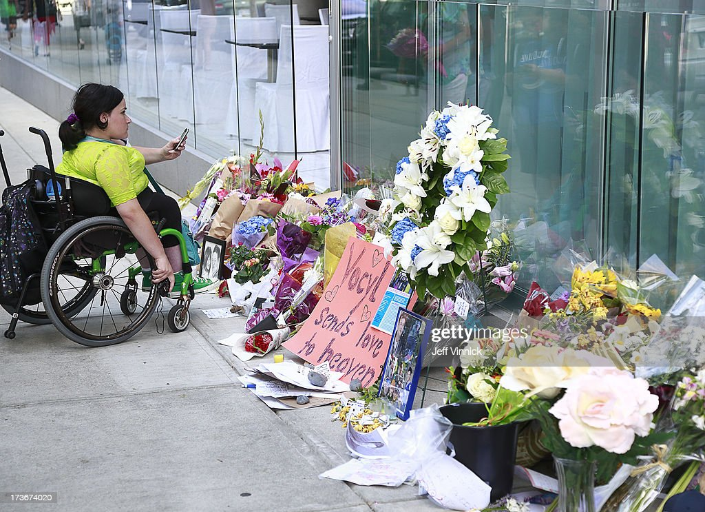 A young woman takes a photo at a memorial to deceased actor Cory Monteith outside the Fairmont Pacific Rim Hotel on July 16, 2013 in Vancouver, British Columbia, Canada. The B.C. Coroners Service released results of Monteith's autopsy today and found the 31-year-old's cause of death was a mixed drug toxicity involving heroin and alcohol.