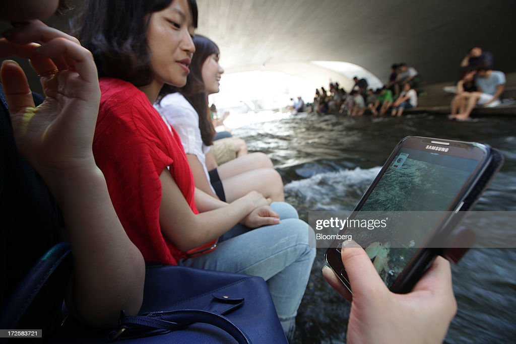 A young woman takes a photograph with a Samsung Electronics Co. smartphone at Cheonggye Stream in Seoul, South Korea, on Wednesday, July 3, 2013. Samsung Electronics lost $25.3 billion in market capitalization last month, more than the value of competitor Sony Corp., as sales of its flagship Galaxy S4 smartphone fell short of investor expectations. Photographer: Woohae Cho/Bloomberg via Getty Images
