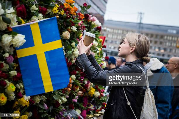A young woman takes a picture of the flowers at the scene of the terrorist truck attack in downtown Stockholm on April 8 2017 in Stockholm Sweden