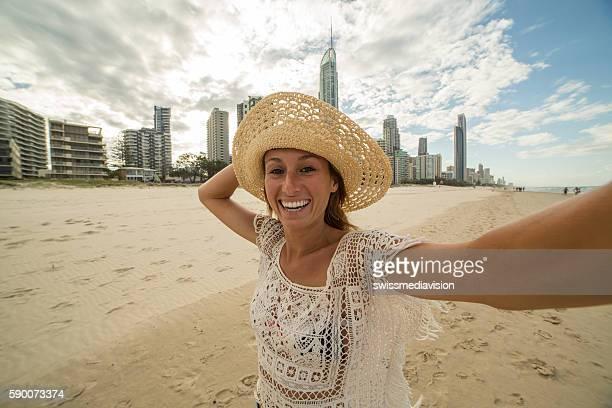 Young woman takes a selfie portrait at Surfer's paradise beach