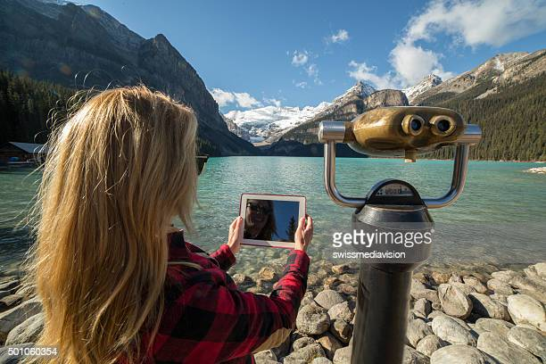 Young woman takes digital tablet pic beside viewer, mtns