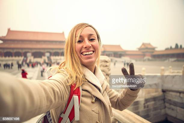 Young woman takes selfie in the Forbidden city, Beijing, China