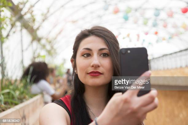 Young woman takes selfie in urban street market.
