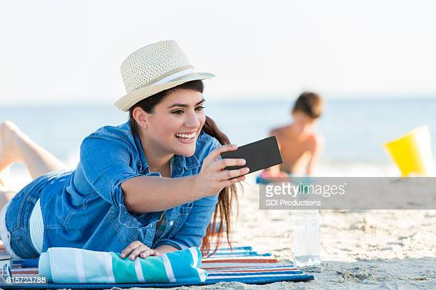 Young woman takes selfie on the beach
