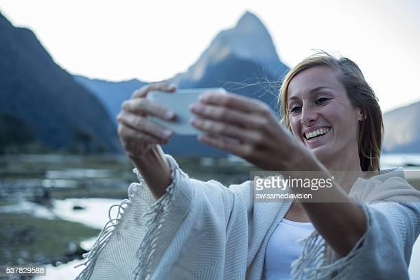 Young woman takes selfie portrait at Mitre peak