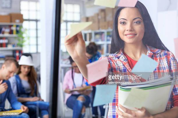 Young woman takes sticky notes from a glass wall