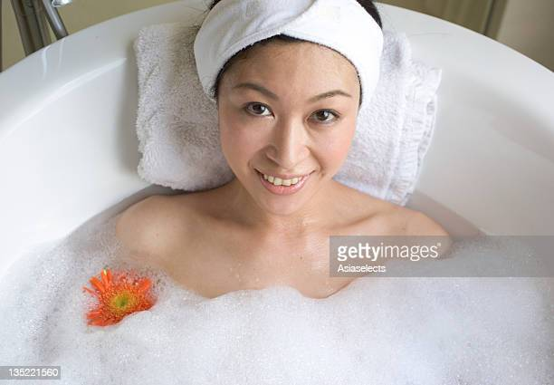 Young woman taking a bath.