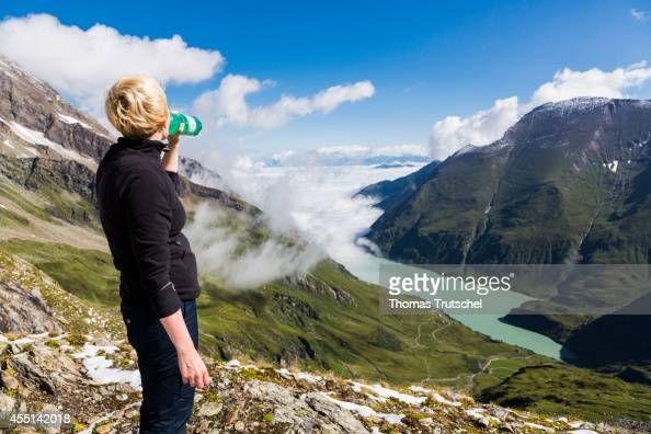 Young woman taking a break and drinking out of a water bottle above the mountain reservoir Mooserboden on August 22 in Mooserboden Austria