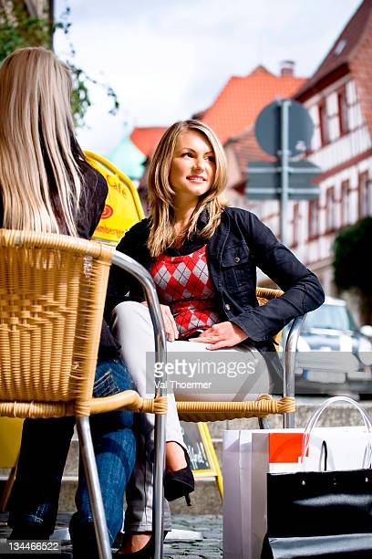 Young woman taking a break from shopping in a street cafe