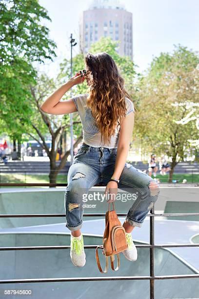 Young woman taking a break in the skateboard park
