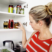 Young woman taking a jar from the kitchen cabinet