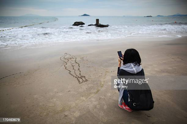 Young woman taking a photo on the beach