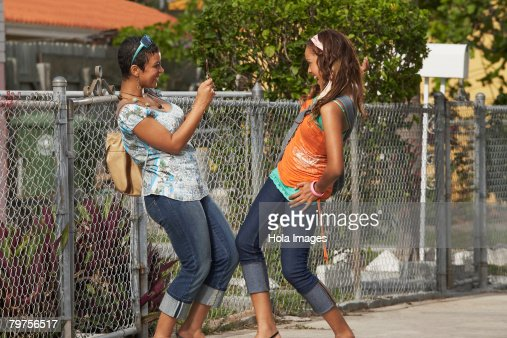 Young woman taking a photograph of her friend