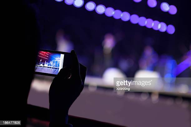 Young woman taking a photography with her smart phone at an indoor concert, over the shoulder view