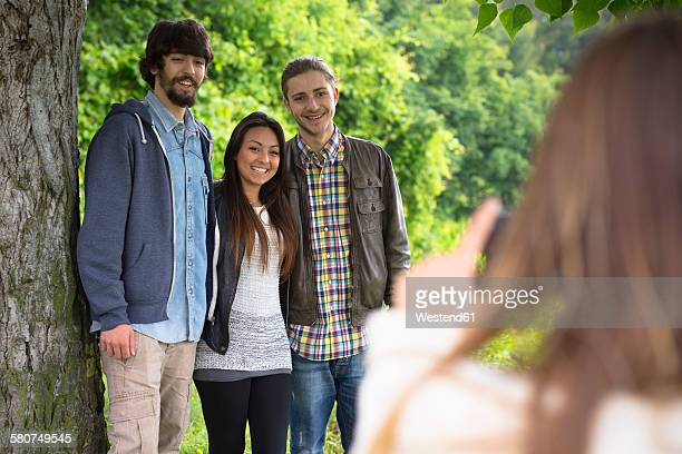 Young woman taking a picture of her three friends