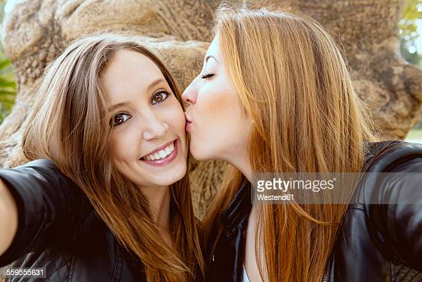 Young woman taking a selfie while her female friend kissing her on the cheek