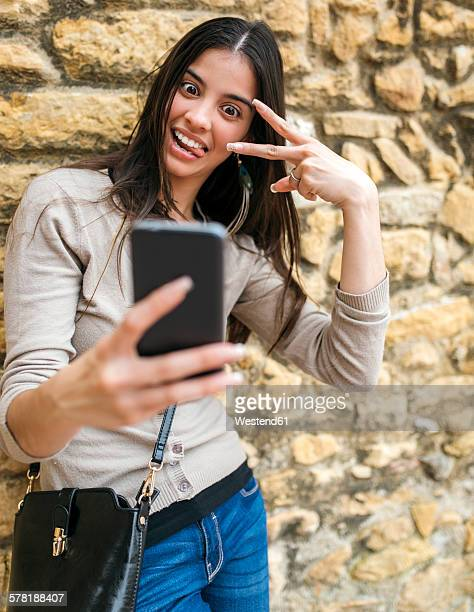 Young woman taking a selfie with her smartphone