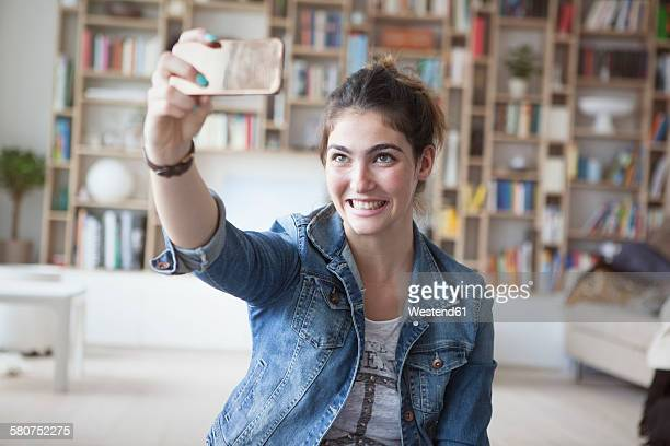Young woman taking a selfie with smartphone at home