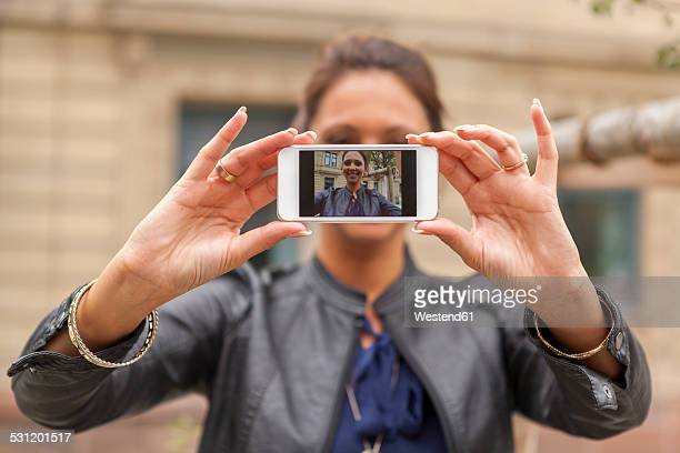 Young woman taking a selfie with smartphone