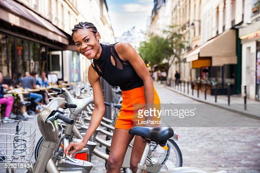 Young woman taking a shared bicycle in Paris