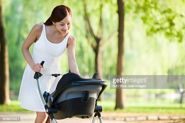 Young woman taking a walk with her baby in pram