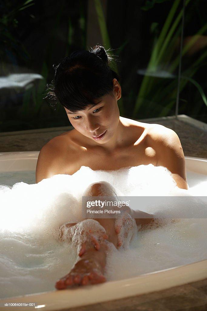Young woman taking bath, washing leg : Stock Photo