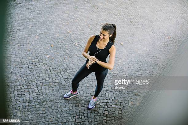 Young woman taking break after jogging in city