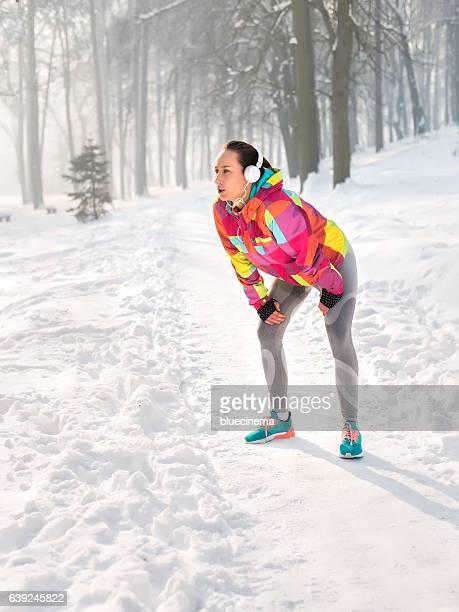 Junge Frau nimmt Atem nach Joggen