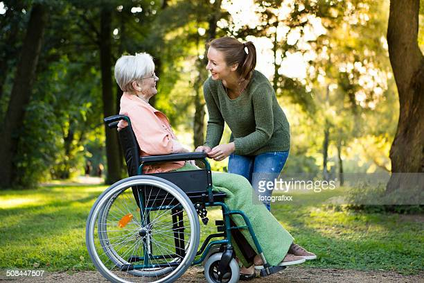 young woman taking care of a senior woman in wheelchair