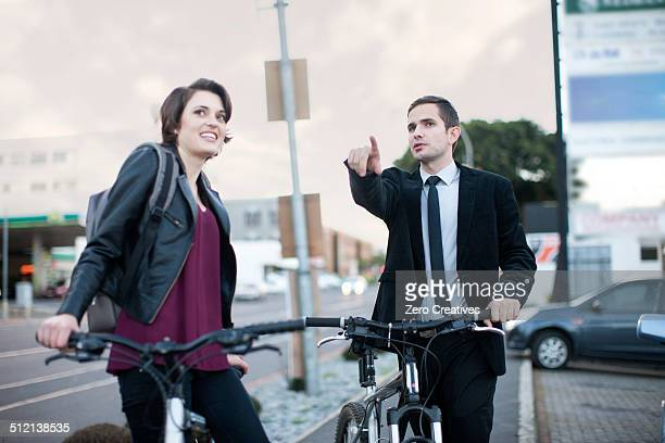 Young woman taking directions from businessman whilst cycling in city