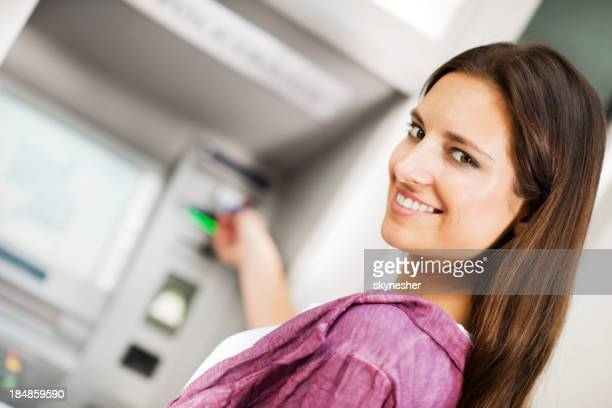 Young woman taking money from ATM.
