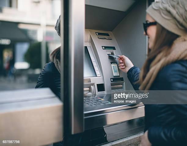 Joven mujer tomando dinero de cajero automático