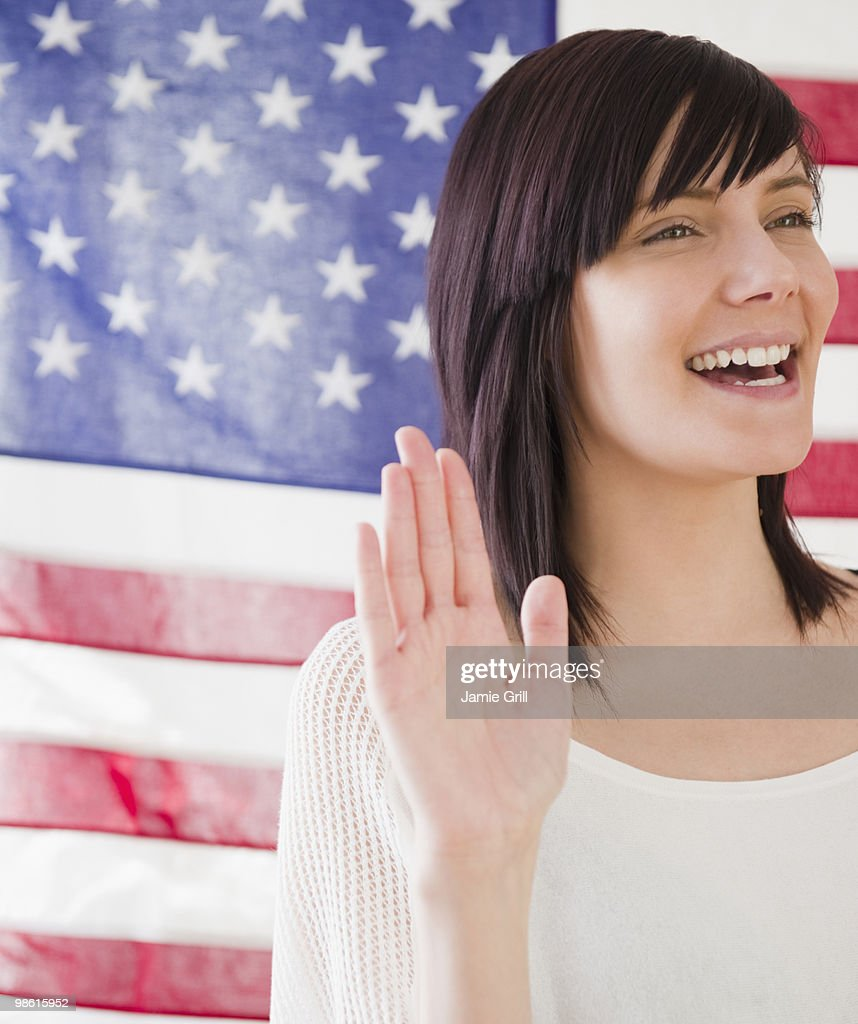 Young woman taking oath in front of American flag : Stock Photo