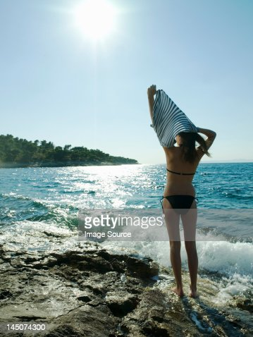 Young woman taking off t-shirt by the sea