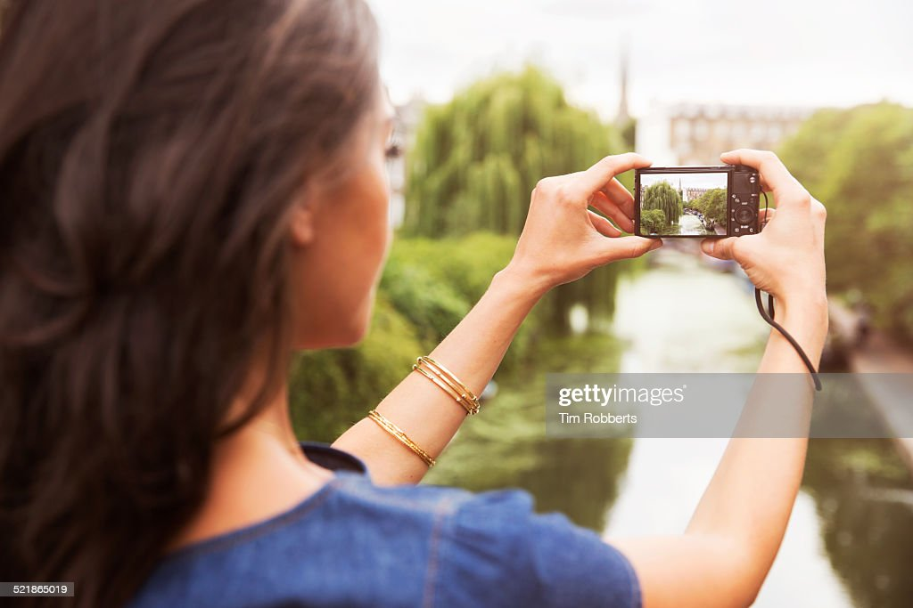 Young woman taking photo of canal.