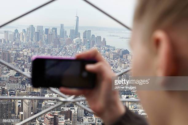 Young woman taking photo of Manhattan with her smartphone, New York City, USA