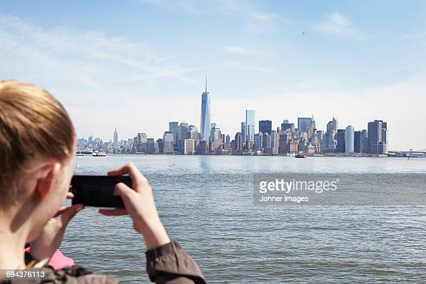 Young woman taking photo of Manhattan with her smartphone