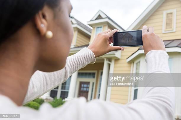 Jeune femme prenant une photo de nouveau chez vous avec le téléphone intelligent