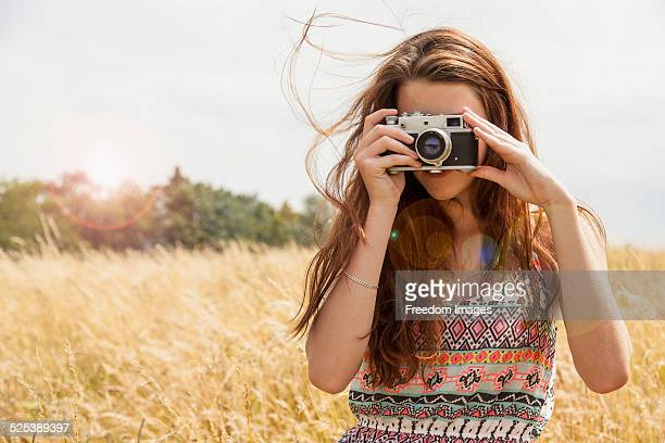 Young woman taking photo with vintage camera in field