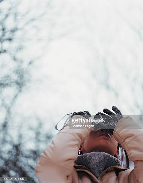 Young woman taking photograph, close-up, winter