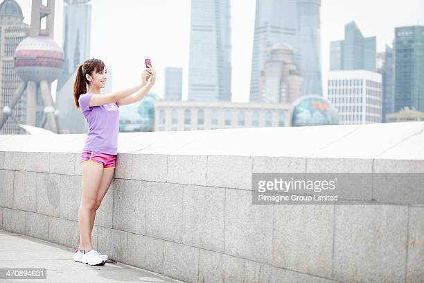 Young woman taking photograph in Shanghai, China