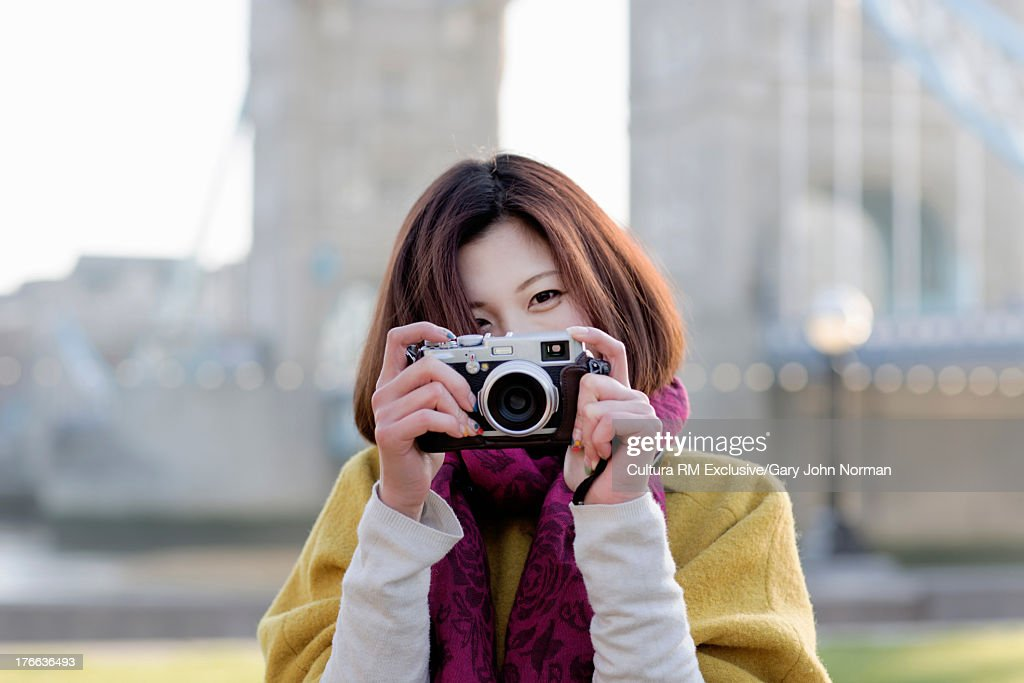 Young woman taking photograph with camera, portrait