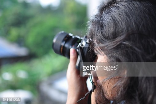 Young woman taking photos with a film camera