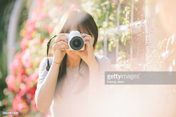 Young woman taking picture in a park