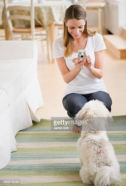 Young woman taking picture of her dog