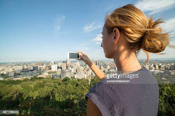 Young woman taking picture of Montreal cityscape