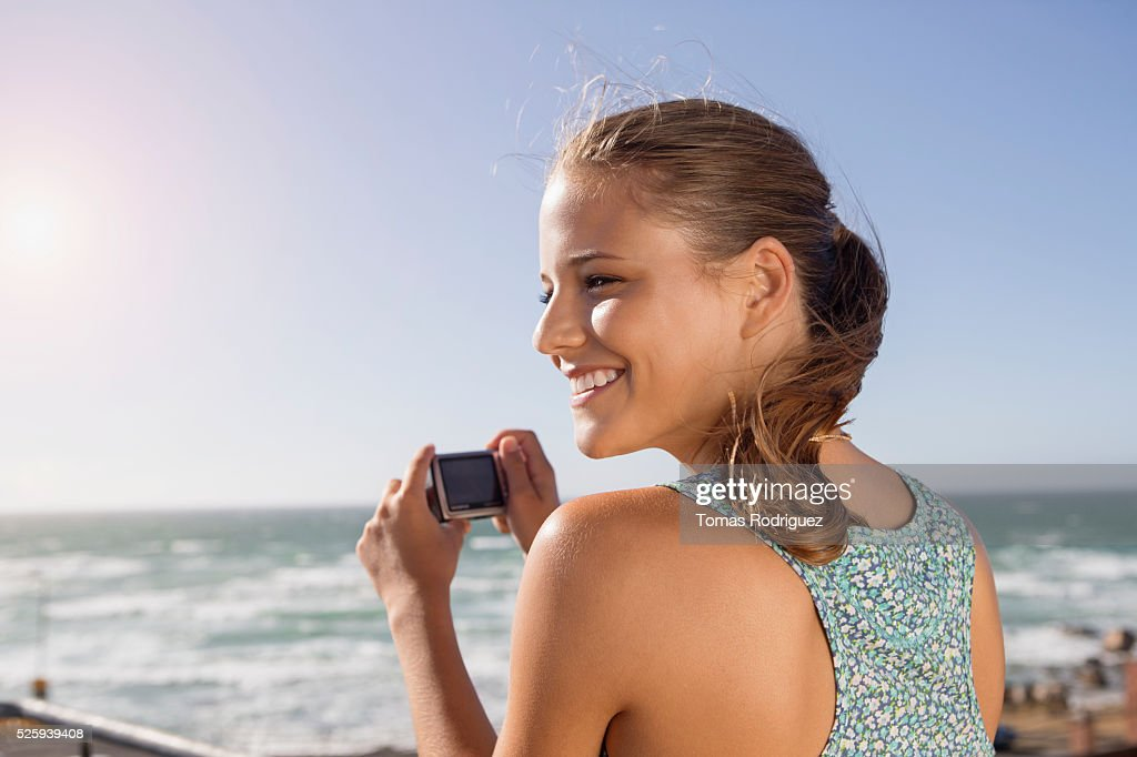 Young woman taking pictures at seaside : Stock-Foto