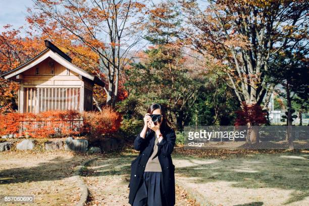 Young woman taking pictures of Autumn foliage in a nature park
